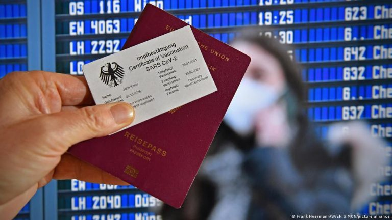 A person is holding a passport and a German vaccine certificate in the same hand.